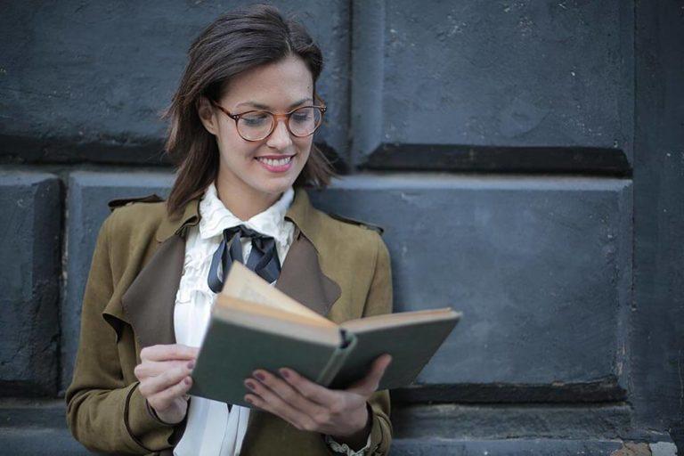 uśmiechnięta kobieta czyta książkę