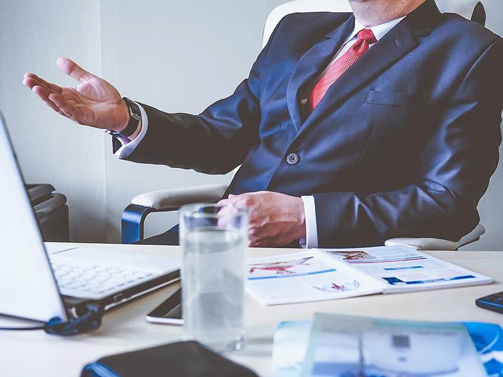 mężczyzna wgarniturze siedzi przy biurku